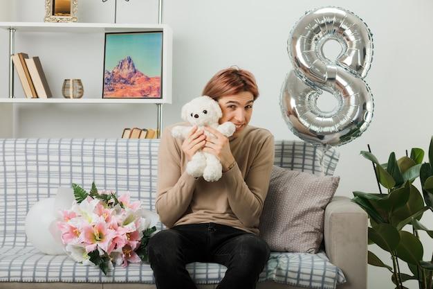 Zadowolony przystojny facet w szczęśliwy dzień kobiet trzymający misia wokół twarzy siedzącej na kanapie w salonie