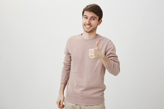 Zadowolony przystojny kaukaski mężczyzna pokazuje kciuk do góry