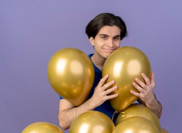 Zadowolony przystojny kaukaski mężczyzna stoi z balonami z helem