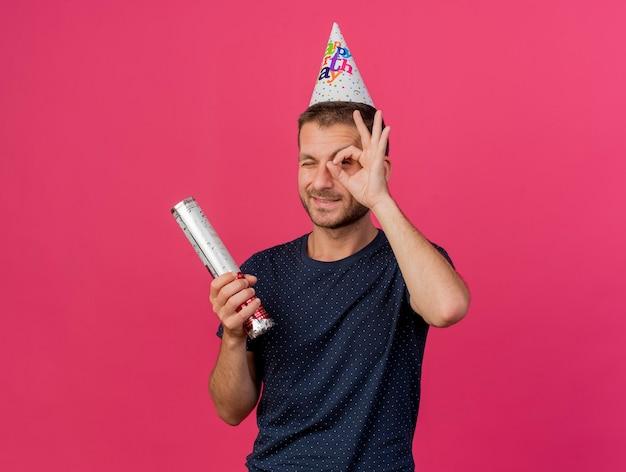 Zadowolony przystojny kaukaski mężczyzna w czapce urodzinowej trzyma armatę konfetti patrząc na kamery przez palce na białym tle na różowym tle z miejsca na kopię