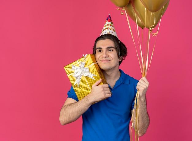 Zadowolony przystojny kaukaski mężczyzna w czapce urodzinowej trzyma balony z helem i pudełko patrząc na bok