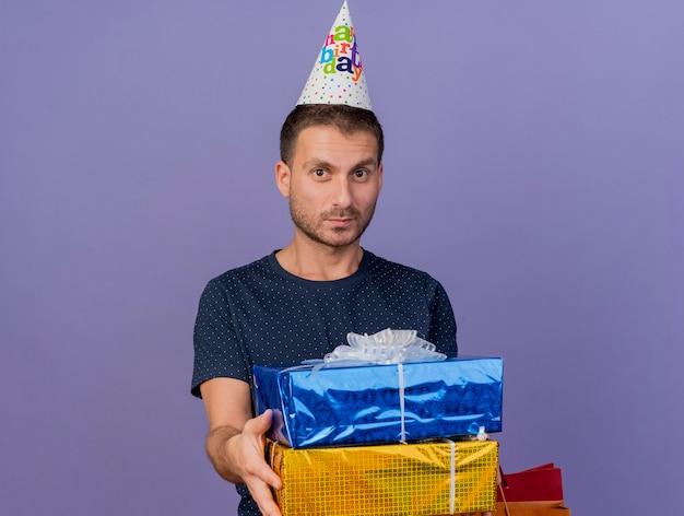 Zadowolony przystojny kaukaski mężczyzna w czapce urodzinowej trzyma pudełka na prezenty i papierową torbę na zakupy na białym tle na fioletowym tle z miejsca na kopię