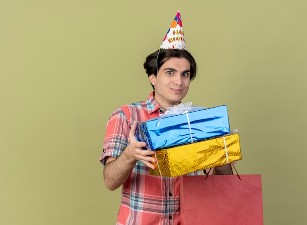 Zadowolony przystojny kaukaski mężczyzna w czapce urodzinowej trzyma pudełka na prezenty i papierową torbę na zakupy