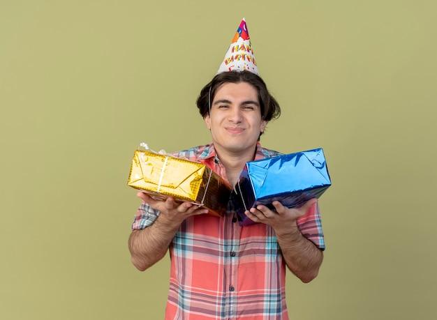 Zadowolony przystojny kaukaski mężczyzna w czapce urodzinowej trzyma pudełka na prezenty