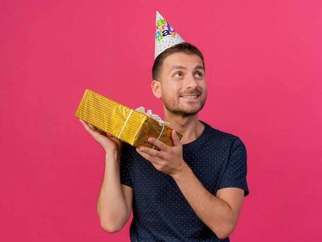 Zadowolony przystojny kaukaski mężczyzna w czapce urodzinowej trzyma pudełko, patrząc z boku na białym tle na różowym tle z miejsca na kopię