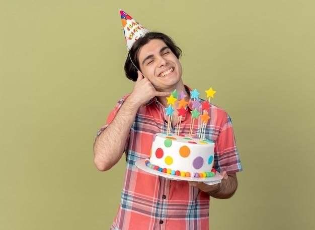 Zadowolony przystojny kaukaski mężczyzna w czapce urodzinowej trzyma tort urodzinowy i gesty zadzwoń do mnie znak me
