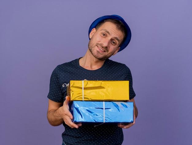 Zadowolony przystojny kaukaski mężczyzna w niebieskim kapeluszu trzyma pudełka, patrząc na kamery na białym tle na fioletowym tle z miejsca na kopię