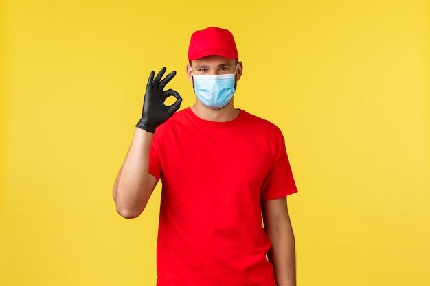 Zadowolony przystojny kurier, czerwony mundur i maska medyczna, zapewniają szybki transfer zamówień klientów, pokazują znak w porządku