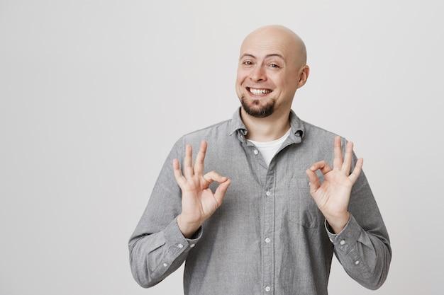 Zadowolony przystojny łysy mężczyzna w średnim wieku pokazuje znak ok