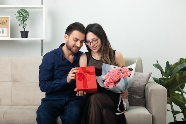 Zadowolony przystojny mężczyzna daje pudełko całkiem młodej kobiecie w okularach optycznych trzymającej bukiet kwiatów siedzący na kanapie w salonie w marcowy międzynarodowy dzień kobiet