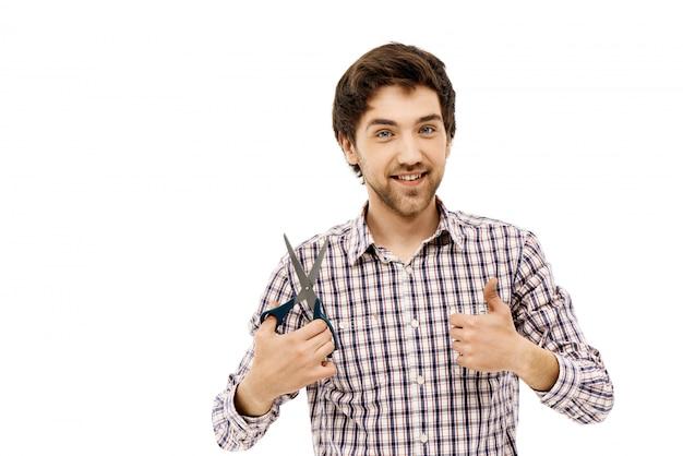 Zadowolony przystojny mężczyzna, kciuk w górę, trzymaj nożyczki