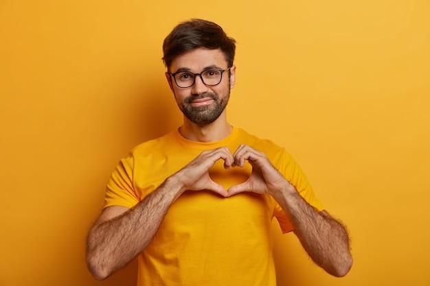 Zadowolony przystojny mężczyzna o gęstym włosiu, układający serce na piersi