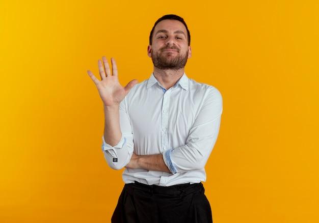 Zadowolony przystojny mężczyzna stoi z podniesioną ręką na białym tle na pomarańczowej ścianie