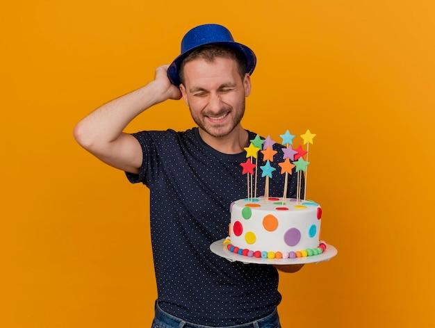 Zadowolony przystojny mężczyzna ubrany i utrzymujący niebieski kapelusz party trzyma tort urodzinowy na pomarańczowej ścianie z miejsca na kopię