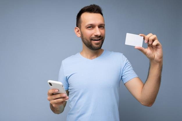 Zadowolony przystojny mężczyzna ubrany w codzienne ubrania na białym tle na ścianie w tle, trzymając i używając telefonu i karty kredytowej dokonywania płatności patrząc na kamery.