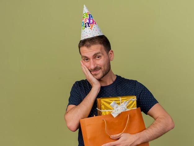Zadowolony przystojny mężczyzna w czapce urodzinowej kładzie rękę na twarzy i trzyma pudełko w papierowej torbie na zakupy odizolowane na oliwkowej ścianie z miejscem na kopię