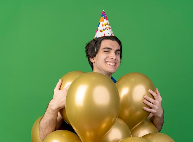 Zadowolony przystojny mężczyzna w czapce urodzinowej trzyma balony z helem na białym tle na zielonej ścianie