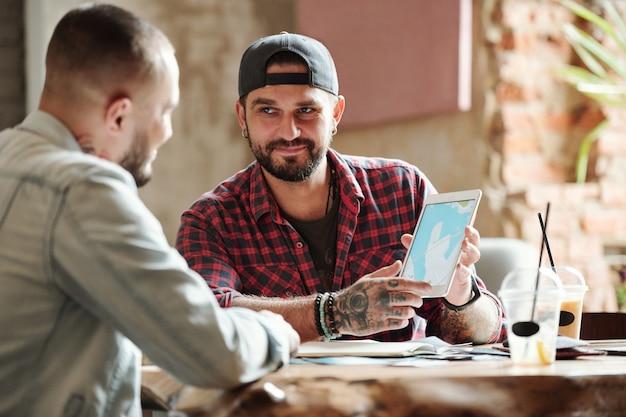 Zadowolony przystojny mężczyzna w czapce z daszkiem, który pokazuje przyjacielowi trasę podróży, planując podróż w kawiarni