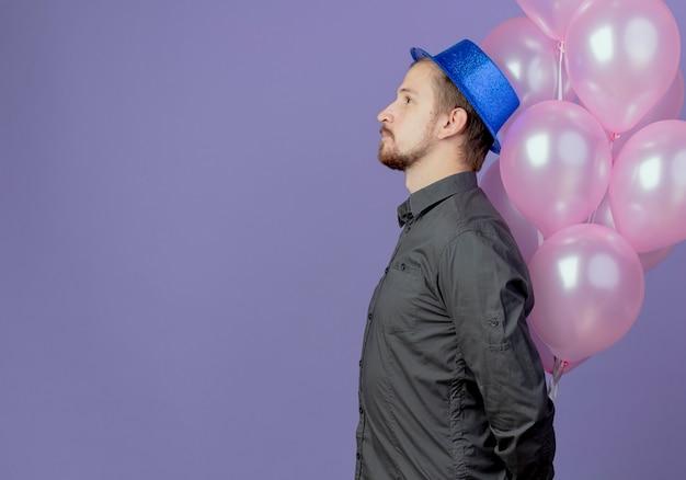 Zadowolony przystojny mężczyzna w niebieskim kapeluszu stoi bokiem z balonami helowymi odizolowanymi na fioletowej ścianie