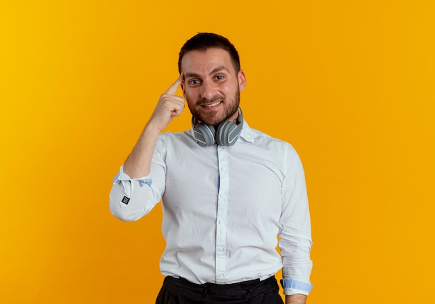 Zadowolony przystojny mężczyzna ze słuchawkami na szyi kładzie palec na skroni odizolowanej na pomarańczowej ścianie