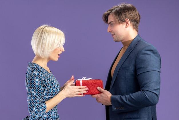Zadowolony przystojny słowiański mężczyzna daje pudełko i patrzy na zaskoczoną ładną blondynkę w walentynki