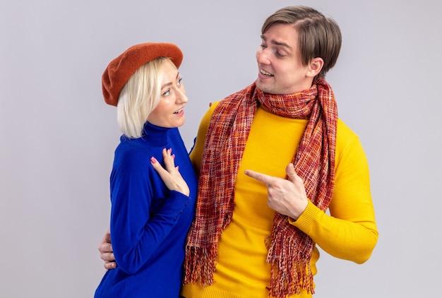 Zadowolony przystojny słowiański mężczyzna z szalikiem na szyi, patrzący i wskazujący na ładną blondynkę z beretem na walentynki