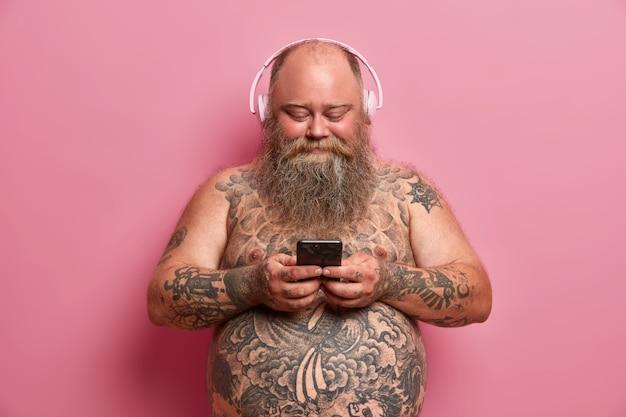 Zadowolony pulchny mężczyzna z nagim, wytatuowanym ciałem, dużym brzuchem, słucha muzyki w słuchawkach, trzyma komórkę, pobiera piosenki z listy odtwarzania, odizolowany na różowej ścianie. ludzie, nadwaga, koncepcja hobby