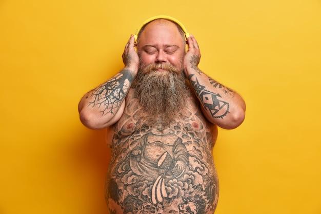 Zadowolony pulchny mężczyzna z przyjemnością słucha muzyki w słuchawkach, zamyka oczy, stoi nago, ma wytatuowane ciało, gruby wystający brzuch, gęsta broda, cieszy się dobrym dźwiękiem, odizolowany na żółtej ścianie