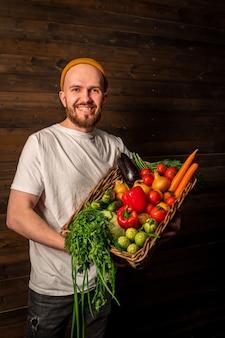 Zadowolony rolnik w białej koszulce i kapeluszu trzyma kosz świeżych owoców i warzyw