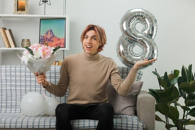 Zadowolony rozłożenie ręki przystojny facet na szczęśliwy dzień kobiet trzyma bukiet, siedząc na kanapie w salonie