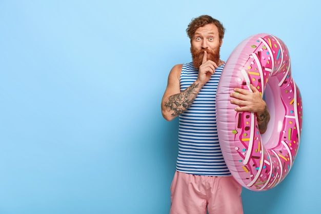 Zadowolony rudy mężczyzna pozuje z pływającym basenem pączków