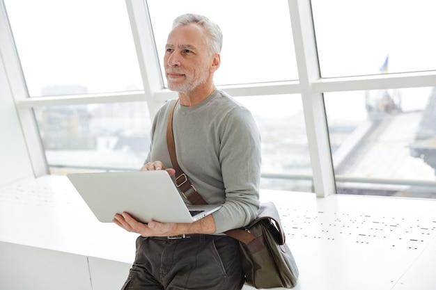 Zadowolony siwy mężczyzna trzymający i używający laptopa stojąc w pobliżu okien w pomieszczeniu