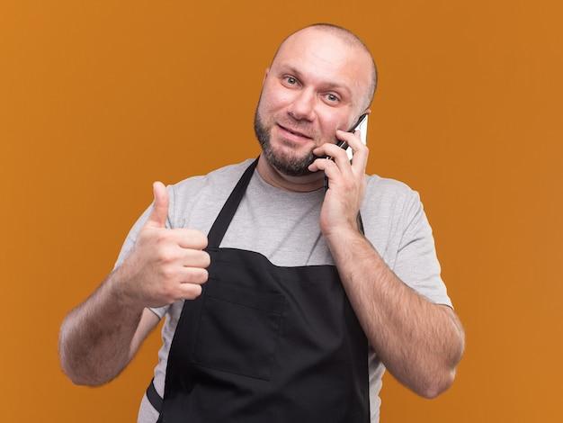Zadowolony słowiański fryzjer męski w średnim wieku w mundurze mówi przez telefon pokazując kciuk do góry na białym tle na pomarańczowej ścianie