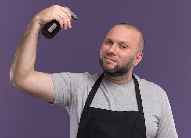Zadowolony słowiański fryzjer w średnim wieku w mundurze podnoszącym butelkę z rozpylaczem na fioletowej ścianie