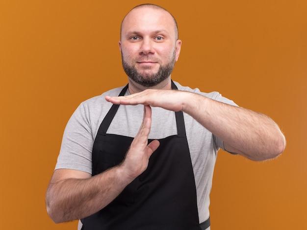 Zadowolony słowiański męski fryzjer w średnim wieku w mundurze pokazujący gest limitu czasu na pomarańczowej ścianie