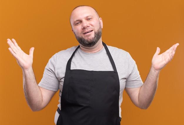Zadowolony słowiański męski fryzjer w średnim wieku w mundurze rozkładającym ręce na pomarańczowej ścianie