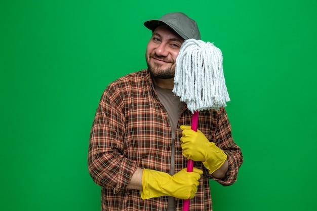 Zadowolony słowiański sprzątacz w gumowych rękawiczkach trzymający mopa