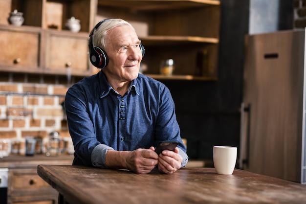 Zadowolony starszy mężczyzna za pomocą swojego smartfona podczas korzystania z laptopa w domu