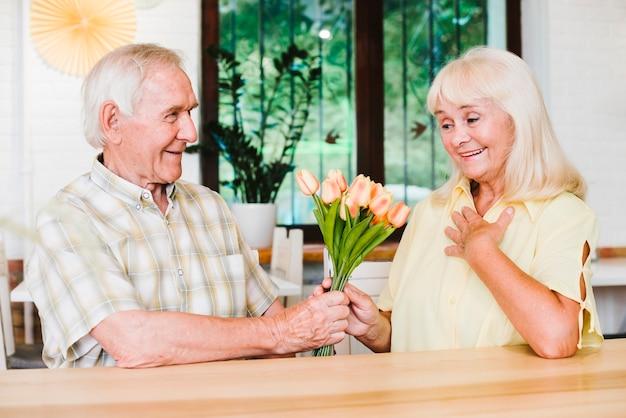 Zadowolony starszy para siedzi w kawiarni i przedstawia kwiaty