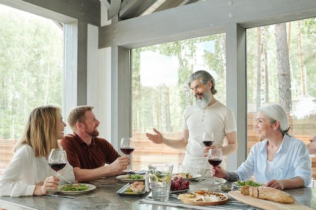 Zadowolony starszy siwobrody ojciec trzymający kieliszek i wznoszący toast na rodzinnym obiedzie