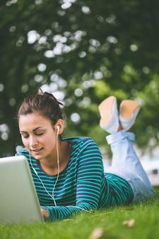 Zadowolony studencki lying on the beach na trawie używać laptop