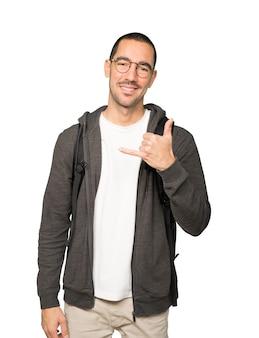 Zadowolony student wykonujący gest wzywania ręką