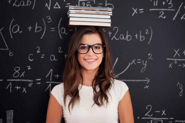 Zadowolony student z książkami na głowie