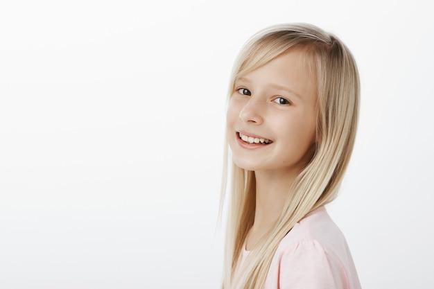 Zadowolony szczęśliwa mała dziewczynka kaukaski z długimi blond włosami, uśmiechając się radośnie