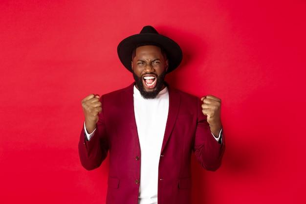 Zadowolony szczęśliwy czarny człowiek świętujący zwycięstwo