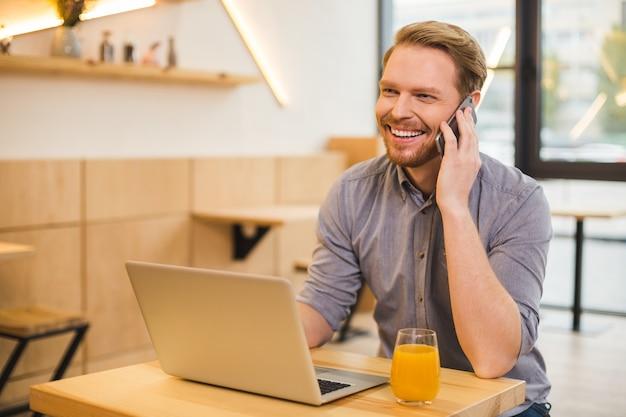 Zadowolony szczęśliwy miły człowiek siedzący przy laptopie i rozmawiając przez telefon będąc w dobrym nastroju
