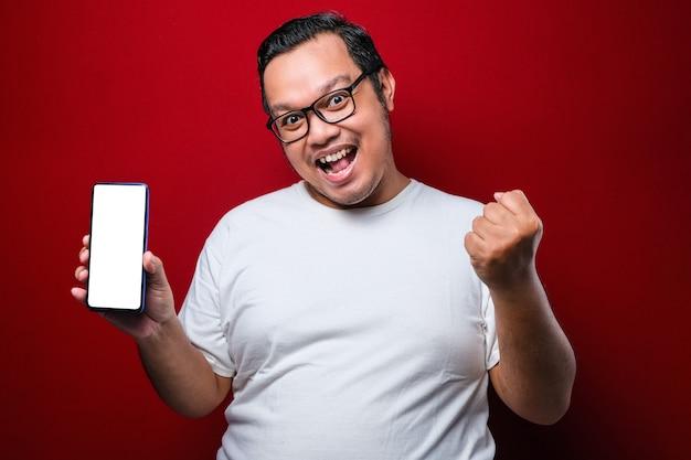 Zadowolony szczęśliwy młody azjatycki facet w białej koszulce uśmiecha się do kamery, trzymając smartfona wskazującego na ekran telefonu komórkowego na czerwonym tle