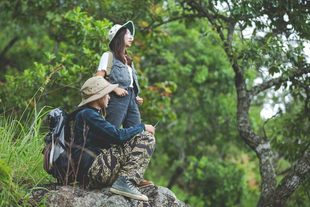 Zadowolony turysta spaceruje po dżungli z plecakiem.