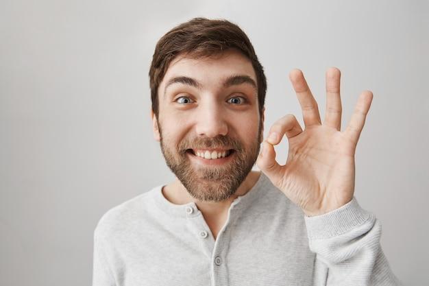 Zadowolony uroczy uśmiechnięty facet pokazuje dobry gest, polecam produkt