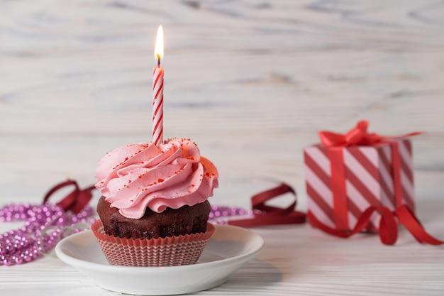 Zadowolony urodziny babeczka z różowym lukrem o smaku wiśniowym z zapaloną świecą